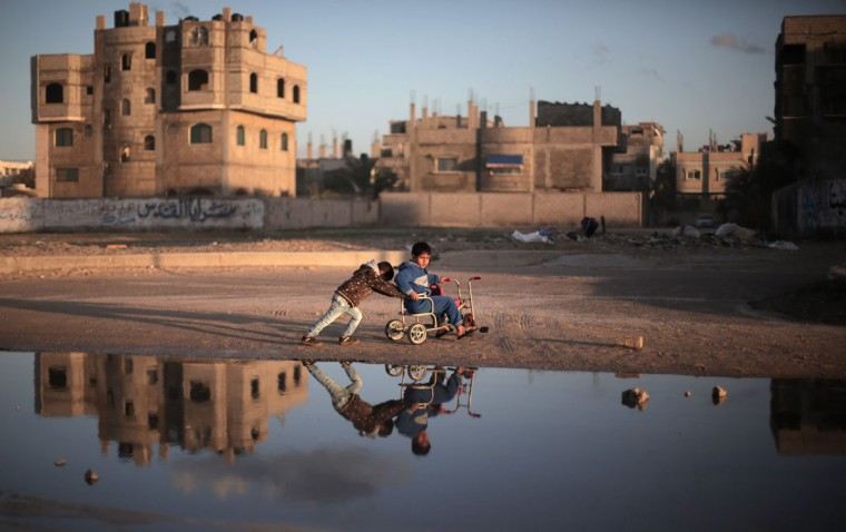 Palestinian children play on the street in Deir el-Balah refugee camp, central Gaza Strip, Saturday, Feb. 21, 2015. (AP Photo/Khalil Hamra)