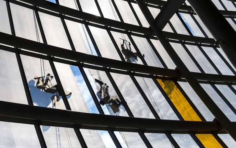 From left to right, Landon Coons, Felipe Fernandez, Vincente Guerrero and Martin Molina (partially hidden), all of MTB Window, clean the exterior glass of the Sprint Center on Tuesday, March 10, 2015, prior to the Big 12 Basketball Tournament this week. Cleaning the interior and exterior glass takes two weeks to complete. (AP Photo/The Kansas City Star, David Eulitt)