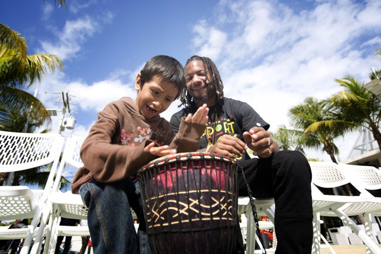 Danny Agnew, from the Dream Defenders group, teaches a young boy, Ismael, to play a drum at a multi-cultural festival, Sunday, Feb. 1, 2015, at Miami's Little Haiti cultural center. (AP Photo/J Pat Carter)