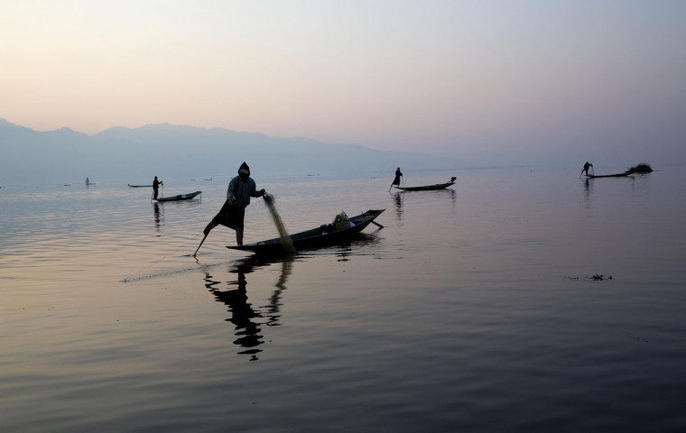 Ethnic Intha fishermen with their legs wrapped around oars pull up nets in Inle lake, northeastern Shan state, Myanmar, Sunday, Feb. 15, 2015. Intha fisherman are known for a unique style of rowing with one leg wrapped around a single oar instead of using their hands. (AP Photo/Gemunu Amarasinghe)