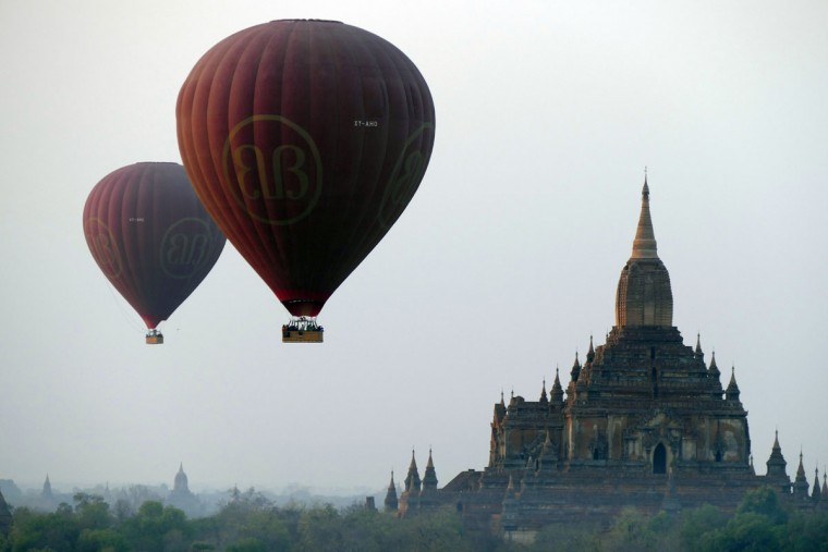 Balloons carrying tourists fly near old temples in Bagan, Myanmar on Tuesday Feb. 24, 2015. (AP Photo/Khin Maung Win)