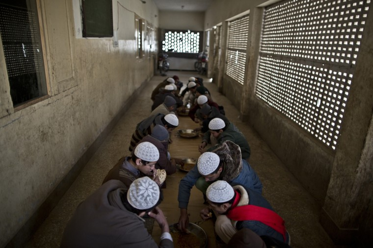 In this Sunday, Feb. 1, 2015 photo, Pakistani students of a madrassa, or Islamic school, eat their lunch at their seminary in Islamabad, Pakistan. Thereís no exact number of madrassas in Pakistan but estimates put the number in the tens of thousands. They provide food, housing and a religious education to students from around the country. Many teach both male and female students. (AP Photo/Muhammed Muheisen)
