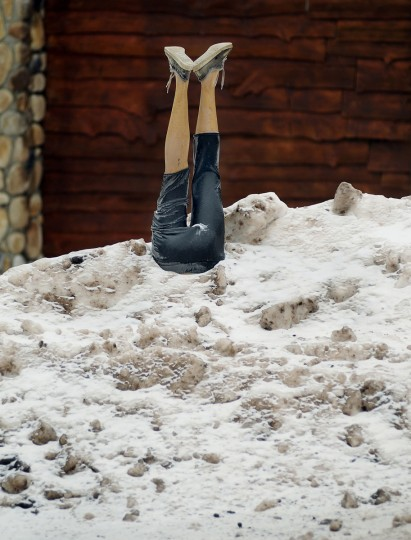 The lower half of a mannequin is stuck in a deep pile of snow and ice in front of a home, Tuesday, Feb. 10, 2015, in Covington Township, Pa. (AP Photo/The Times & Tribune, Butch Comegys)