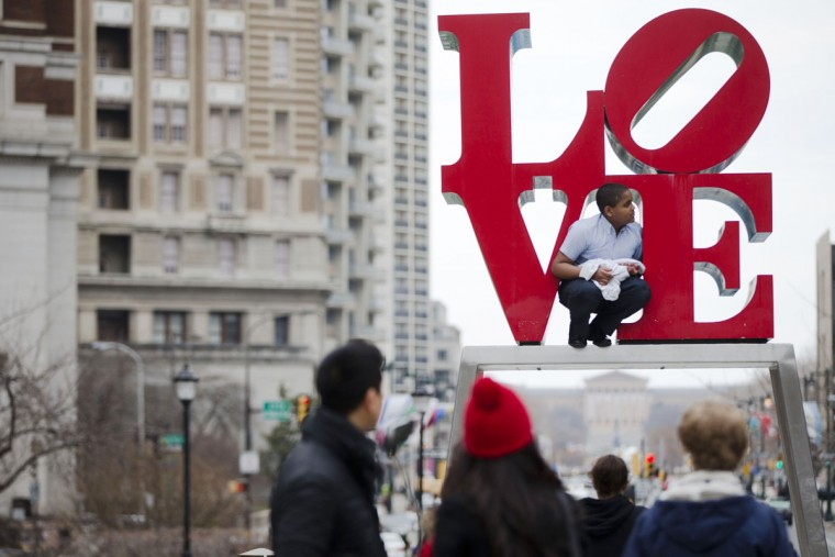 A young man climbs on a sculpture by Robert Indiana, Friday, March 27, 2015, at JFK Plaza, commonly known as Love Park, in Philadelphia. (AP Photo/Matt Rourke)