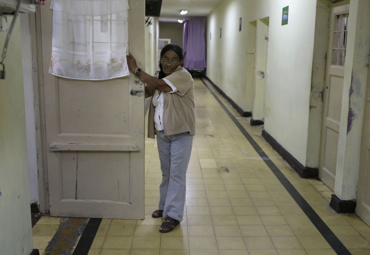 In this Jan. 30, 2015 photo, Carmen Jimenez, 77, stands in front of her prison cell at the Santa Monica women's prison in Lima, Peru. She is one of 2,500 inmates over 60 in the South American countryís prisons. Most of the women over 60 years of age, like Jimenez, are behind bars for drug trafficking. (AP Photo/Martin Mejia)
