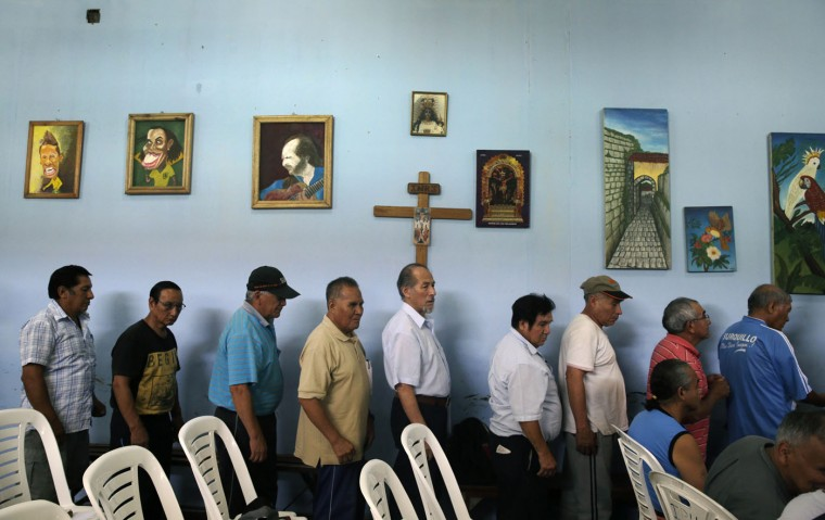 In this Feb. 27, 2015 photo, elderly inmates stand in line for their breakfast of oatmeal and bread, against a wall decorated with religious icons and art work created by the inmates, at Lurigancho men's prison in Lima, Peru. Authorities will only grant pardons or commute sentences in cases where an inmate of more than 65 years of age has serious health problems. (AP Photo/Martin Mejia)