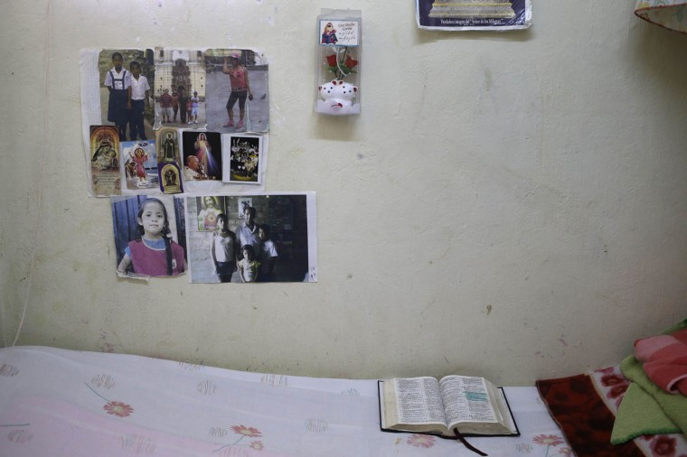 In this Jan. 30, 2015 photo, a wall inside Luz Angelica Ludena's prison cell is decorated with prayer cards and images of her husband and grandchildren, inside the Santa Monica women's prison in Lima, Peru. Ludena, who is serving her second prison term for drug trafficking, takes advantage of the dozens of workshops offered by the prison, but at night she finds solace reading the Bible. (AP Photo/Martin Mejia)