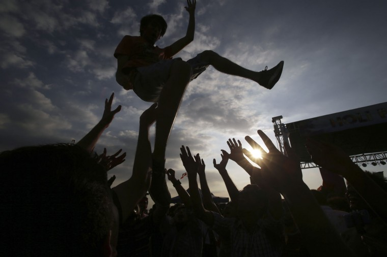 An Indian national is thrown in the air by his friends as they join celebrations of the Holi festival in suburban Pasay, south of Manila, Philippines, on Sunday, March 1, 2015. The event is led by Indian nationals as they mark Holi, a Hindu spring festival also known as festival of colors. (AP Photo/Aaron Favila)
