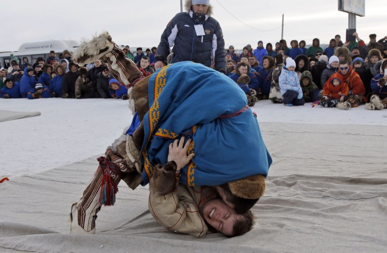 In this photo taken on Saturday, March 14, 2015, Nenets men wrestle during a competition at the Reindeer Herder's Day in the city of Nadym, in Yamal-Nenets Region, 2500 kilometers (about 1553 miles) northeast of Moscow, Russia. For the indigenous nomadic Nenets people, the Reindeer Herderís Day offers a chance to show their prowess in wrestling, high jumps and other traditional local sports, but, above all, reindeer races. (AP Photo/Dmitry Lovetsky)