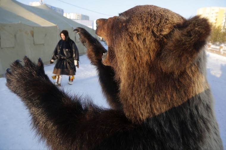 In this photo taken on Sunday, March 15, 2015, a Nenets man walks part a stuffed bear at the Reindeer Herder's Day in the city of Nadym, in Yamal-Nenets Region, 2500 km (about 1553 miles) northeast of Moscow, Russia. The Reindeer Herder's Day is celebrated annually in Russiaís Yamal-Nenets region in the Arctic and for the Nenets people, it offers a chance to show their prowess in wrestling, high jumps and other traditional sports, but, above all, reindeer races. (AP Photo/Dmitry Lovetsky)
