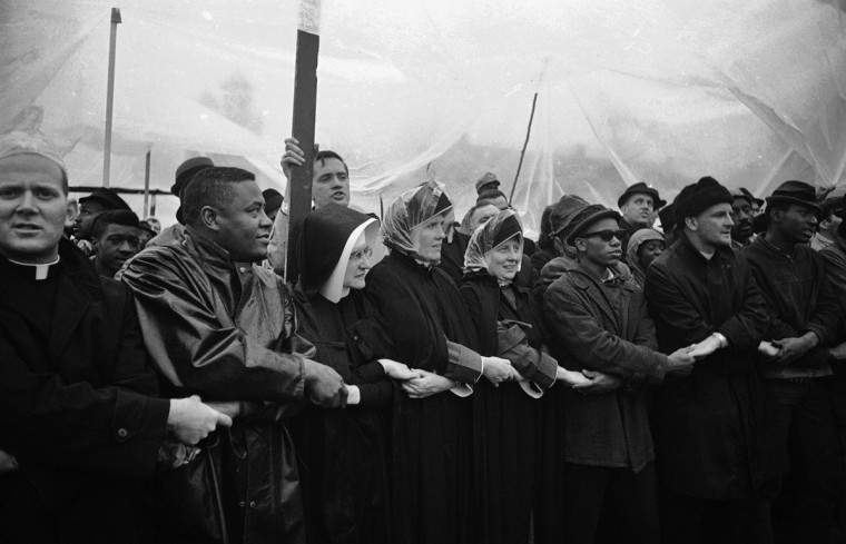 In this March 13, 1965 file photo, three unidentified nuns from the Queen of the World Hospital in Kansas City join hands with other demonstrators under a tarp to sing freedom songs in Selma, Ala. This group stood for two days, mostly in the rain, in a voter registration protest. (AP Photo/File)
