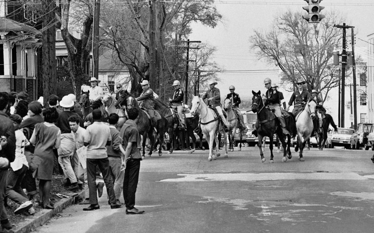 In this March 16, 1965 file photo, mounted state and county police officers ride their horses into a group of demonstrators after they refused to disperse in Montgomery, Ala. (AP Photo/Perry Aycock)