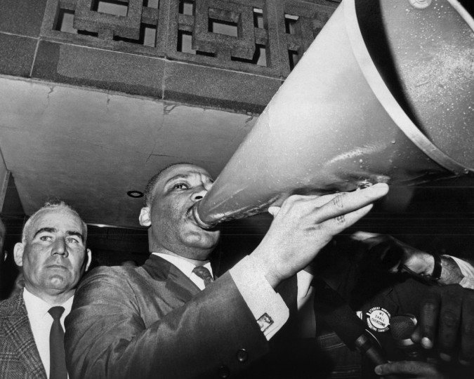 In this March 17, 1965 file photo, Dr. Martin Luther King Jr. uses a megaphone to address demonstrators assembled at the courthouse in Montgomery, Ala. after a meeting with Sheriff Mac Butler, left, and other public officials. (AP Photo/File)