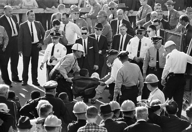 In this March 18, 1965 file photo, police carry a demonstrator into a police vehicle after a group picketed in Montgomery, Ala. and refused to disperse after an hour and a half. About 80 were arrested in front of the Alabama state capitol building. (AP Photo/File)