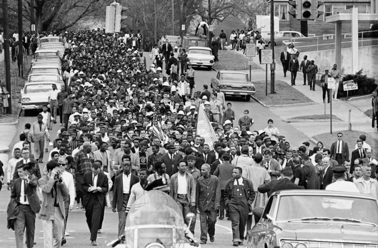 In this March 17, 1965 file photo, thousands of demonstrators march to the Montgomery, Ala. courthouse behind Dr. Martin Luther King Jr. to protest treatment of demonstrators by police during an attempted march. At foreground center in white shirt is Andrew Young. (AP Photo/File)