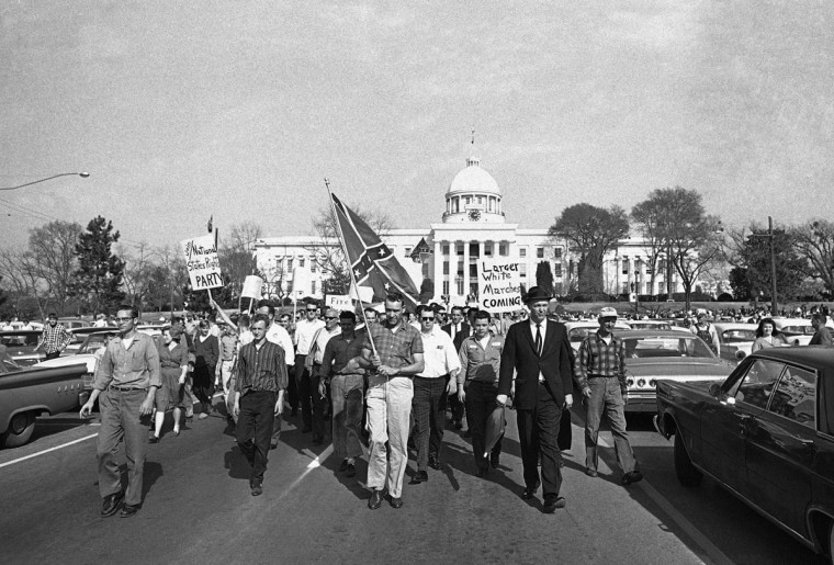 In this March 18, 1965 file photo, members of the Organization for Better Government march with a Confederate flag away from the capitol in Montgomery, Ala. They stopped within 25 feet of voter registration rallies, had several speeches, then marched off again. (AP Photo/File)