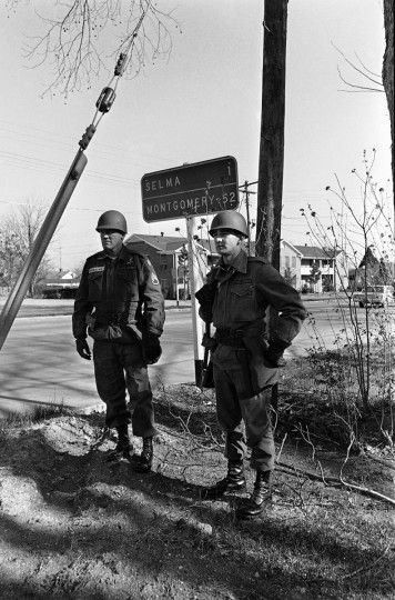 In this March 20, 1965 file photo, National Guardsmen, called to active federal duty by President Lyndon B. Johnson to protect marchers planning to march from Selma, Ala. to the state capitol at Montgomery, stand under a road sign showing the distance to the capital. The demonstration ended at the capitol building in a rally protesting voting regulations in Alabama. (AP Photo/File)