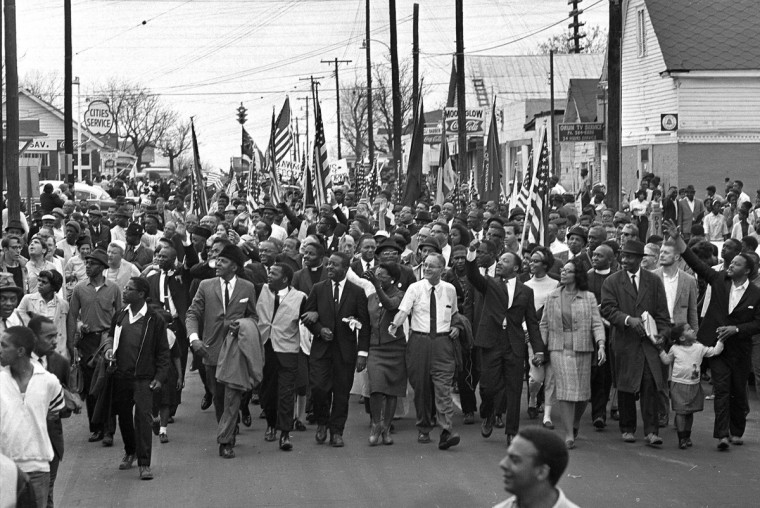 In this March 21, 1965 file photo, Dr. Martin Luther King, foreground row, fifth from right, waves as marchers stream across the Alabama River on the first of a five day, 50-mile march to the state capitol at Montgomery, Ala. (AP Photo/File)