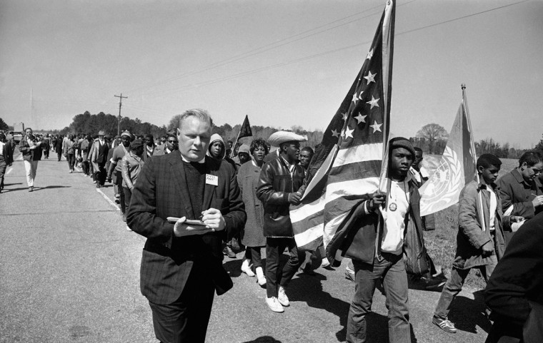 In this March 22, 1965 file photo, New York Post Writer David Murray walks with civil rights marchers about ten miles from Selma, Ala. on their 50-mile walk to the state capital in Montgomery, Ala. to protest voting laws in Alabama. (AP Photo/File)