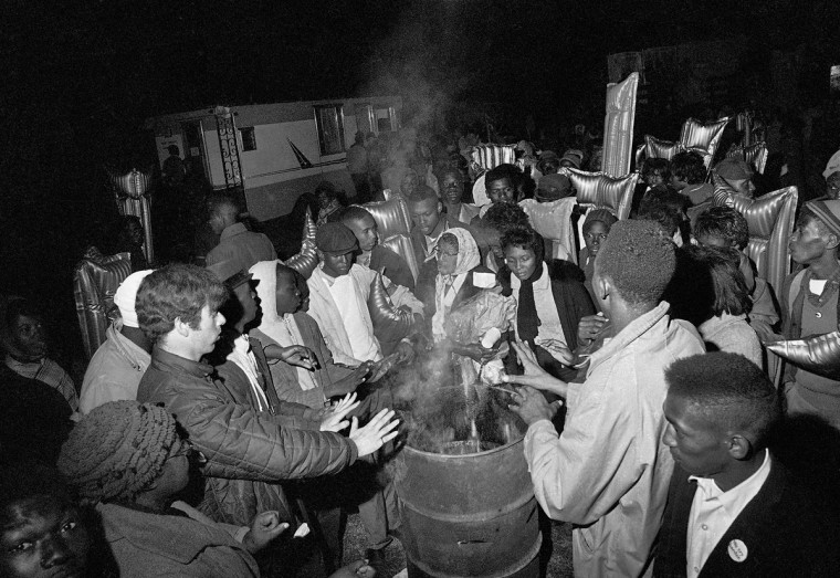 In this on March 22, 1965 file photo, participants in first leg of the 50-mile march from Selma, Ala. to the Alabama state capitol at Montgomery, Ala., warm themselves around a fire in an oil drum at the first night's camp in Selma. The marchers, protesting voting laws in the state, walked along Route 80 for approximately seven miles before making camp for the night. (AP Photo/File)