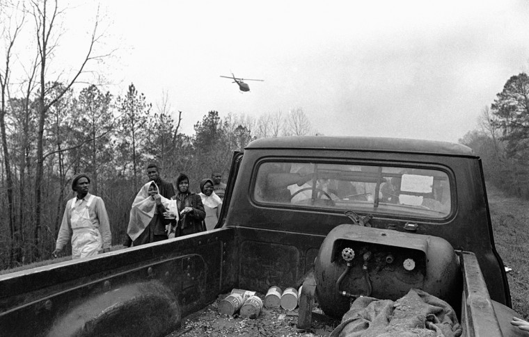 In this March 23, 1965 file photo, civil rights marchers in Selma, Ala. walk past a trucker with a shotgun mounted in the cab along Route 80 during their march to the state capitol in Montgomery, Ala. Marchers' reactions ranged from apparent nervousness to laughs as the truck went by. An army helicopter, part of the force guarding marchers on the trek from Selma passes overhead. (AP Photo/File)