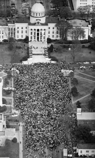 In this March 25, 1965 file photo, civil rights marchers form a crowd in front of the Alabama State Capitol in Montgomery, Ala. at the end of their five-day march from Selma, Ala. to protest discrimination against African-Americans in the state's voting practices. A line of guards stretches across the Capitol steps, upper center, but no attempt was made by marchers to enter the Capitol. (AP Photo/Bill Achatz)