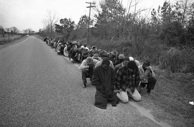 In this March 5, 1965 file photo, about 150 African Americans pray along a roadside near Camden, Ala. after they were stopped by the mayor and deputies from marching into the city to demonstrate against voting laws. (AP Photo/File)