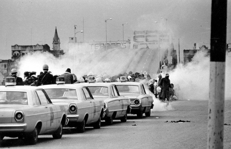 "In this March 7, 1965 file photo, clouds of tear gas fill the air as state troopers, ordered by Gov. George Wallace, break up a demonstration march in Selma, Ala., on what became known as ""Bloody Sunday."" The incident is widely credited for galvanizing the nation's leaders and ultimately yielded passage of the Voting Rights Act of 1965. (AP Photo/File)"