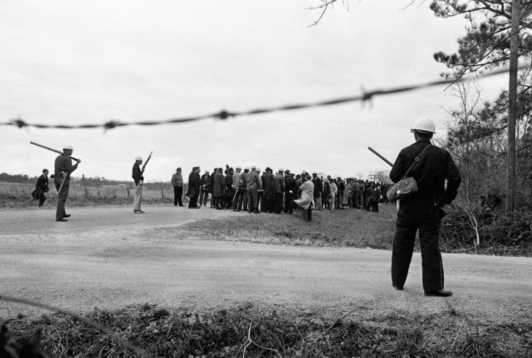 In this March 5, 1965 file photo, the mayor and his auxiliary police, armed with shotguns, rifles, pistols and tear gas, form a roadblock at city limits to stop 150 African Americans from marching into town to the courthouse in a demonstration for voting rights in Camden, Ala. The protesters knelt down and prayed and returned to a church about three miles away. (AP Photo/File)