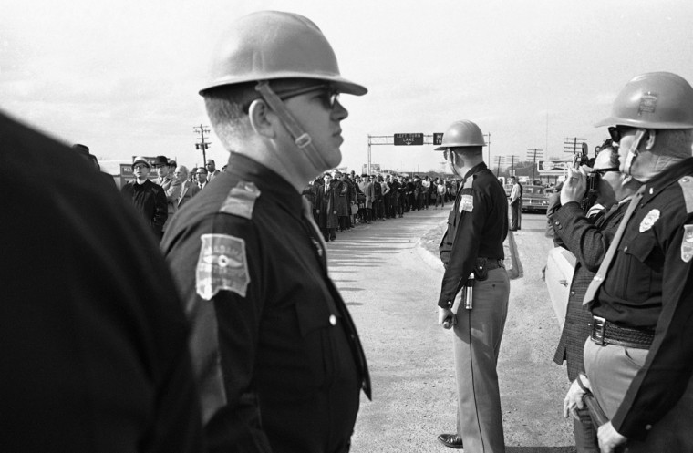 In this March 10, 1965 file photo, a long line of demonstrators approaches a contingent of state troopers who turned them back during a voters rights march at Selma, Ala. The group returned to a church with no incident. (AP Photo/File)