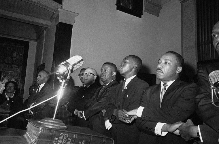 "In this March 9, 1965 file photo, Dr. Martin Luther King, Jr., joins hands with other African American leaders singing ""We Shall Overcome"" at a church rally in Selma, Ala. (AP Photo/File)"