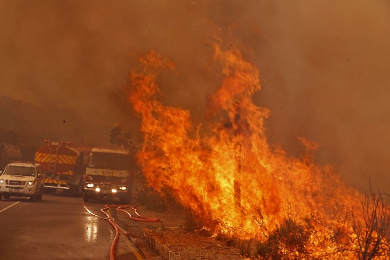 Fire fighters battle a fire near the town of Hout Bay, South Africa, Monday, March 2, 2015. South African firefighters say they are battling to control a wildfire that has burned down five homes in Cape Town's southern peninsula. (AP Photo/Schalk van Zuydam)