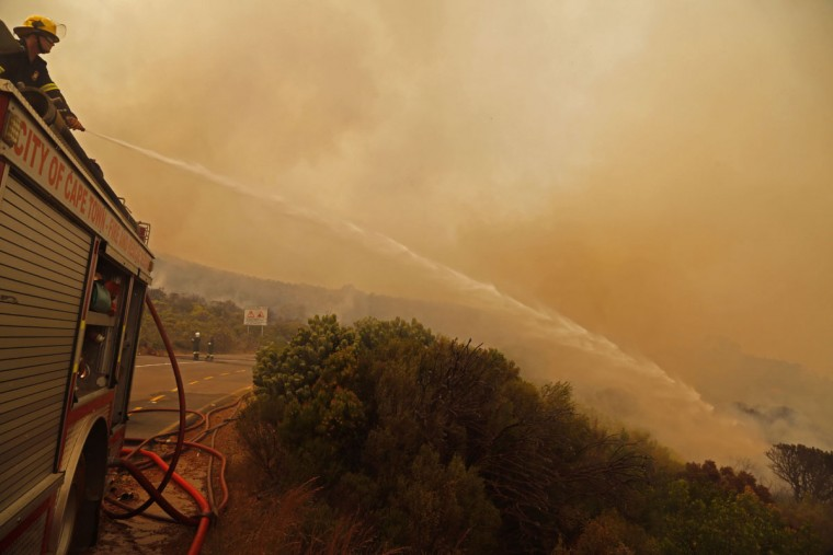 Fire fighters battle a fire near the town of Hout Bay, South Africa, Monday, March 2, 2015. (AP Photo/Schalk van Zuydam)