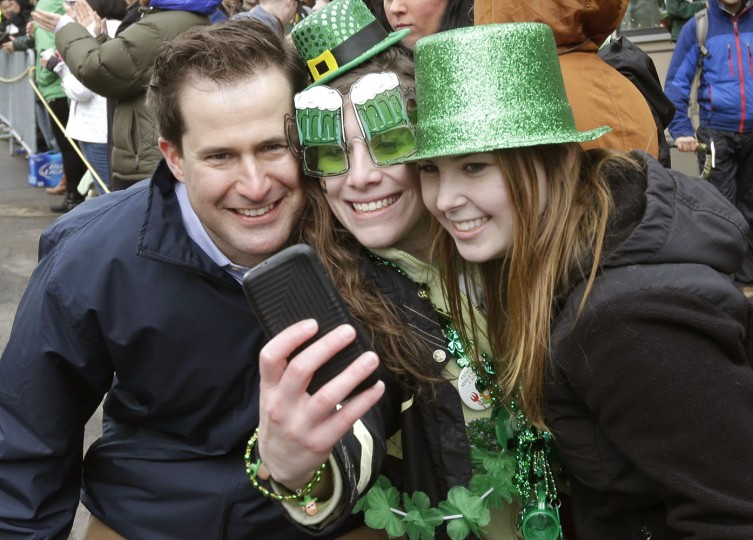 U.S. Rep. Seth Moulton, D-Mass., left, poses for a photo with spectators while marching in the St. Patrick's Day parade, Sunday, March 15, 2015, in Boston's South Boston neighborhood. Until now, gay rights groups have been barred by the South Boston Allied War Veterans Council from marching in the parade, which draws as many as a million spectators each year. Moulton marched with OutVets, a group of gay military veterans, in the parade Sunday. (AP Photo/Steven Senne)