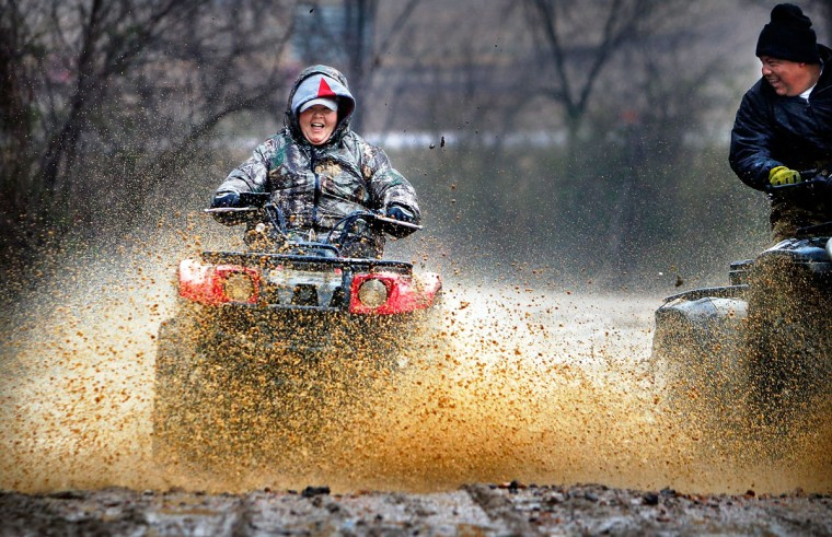 While much of Memphis stayed indoors out of the drizzling cold rain, Vallorie Higgins, left, and Omar Tellez take advantage of the wet day to fly through mud holes along Covington Pike near the Wolf River in Memphis, Tenn., Sunday, March 1, 2015. (AP Photo/The Commercial Appeal, Jim Weber)