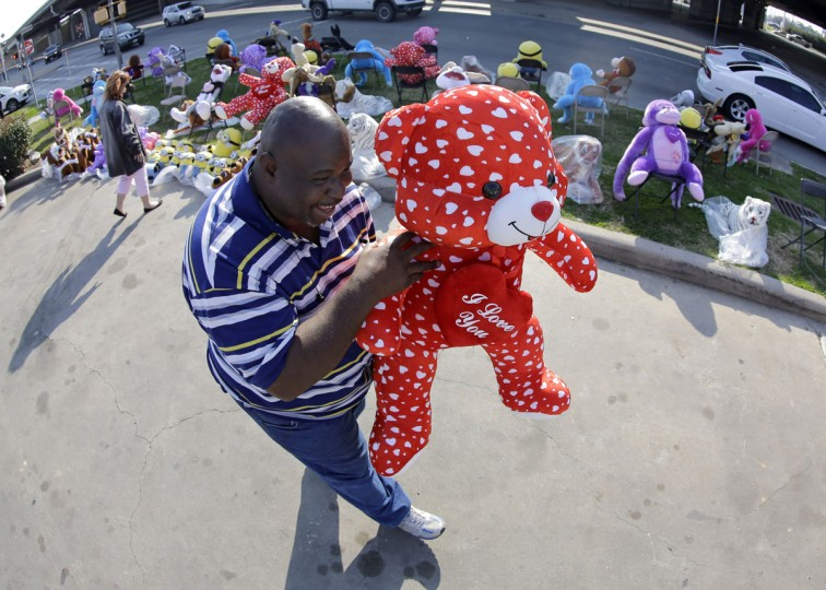 James Scott carries a stuffed animal after purchasing it as a Valentine's Day gift Thursday, Feb. 12, 2015, in Houston. Valentine's Day is Saturday. (AP Photo/David J. Phillip)