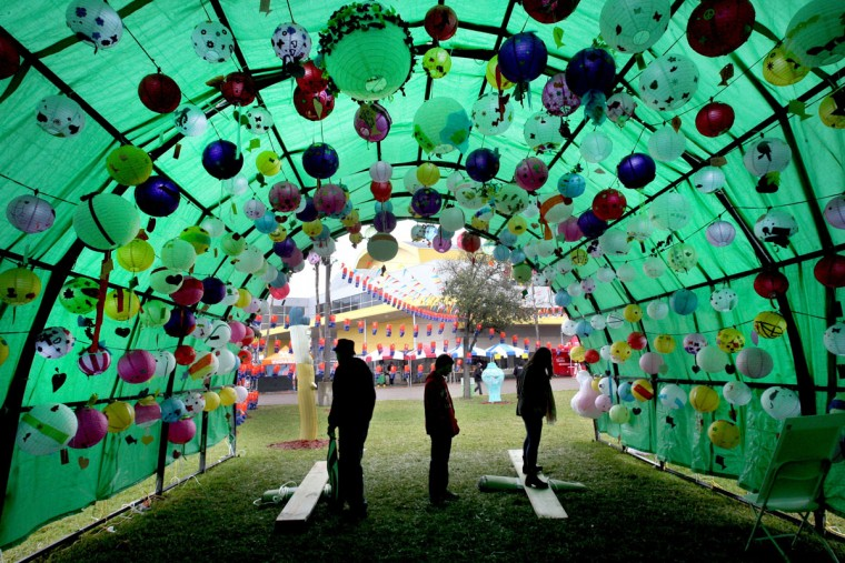Borderfest 2015 goers walk under a colorful tent filled with Asian lanterns made by local school children in Hidalgo, Texas, Sunday, March, 8, 2015. (AP Photo/The Monitor, Delcia Lopez)