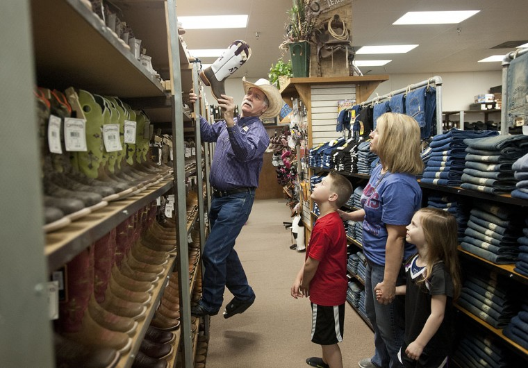 Cavender's employee of 16 years Robert Weesner assists Casey Wilkerson of Canton, Texas, and her children Jake Wilkerson, 8, and Ellie Wilkerson, 4, in finding the right sized boots Tuesday March 24, 2015 at their Tyler, Texas location. This year marks their 50th anniversary of Cavender's. (AP Photo/The Tyler Morning Telegraph, Sarah A. Miller)