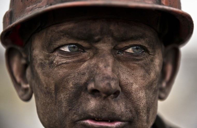 An Ukrainian coal miner waits for a bus after exiting the underground of the Zasyadko mine, where he helped search for bodies of colleagues and clear up debris following an explosion, in Donetsk, Ukraine, Wednesday, March 4, 2015. (AP Photo/Vadim Ghirda)