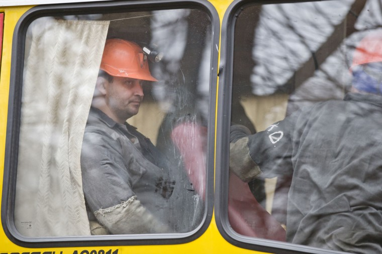 Miners sit on a bus after an explosion at the Zasyadko coal mine in Donetsk, Ukraine Wednesday March 4, 2015. An explosion took place underground at the Zasyadko coal mine in war-torn eastern Ukraine on Wednesday, an area controlled by pro-Russian rebels. (AP Photo/Vadim Ghirda)