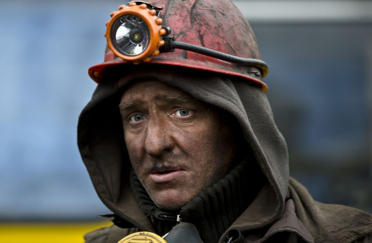 A Ukrainian coal miner walks after exiting the underground of the Zasyadko mine in Donetsk, Ukraine, Wednesday, March 4, 2015. An explosion ripped through a coal mine before dawn Wednesday in war-torn eastern Ukraine, killing at least one miner and trapping more than 30 others underground, rebel and government officials said. One injured miner reported seeing five bodies.(AP Photo/Vadim Ghirda)