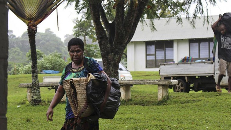 In this photo provided by non-profit organization 350.org, a woman, left, and man gather items in Port Vila, Vanuatu, Saturday, March 14, 2015, in the aftermath of Cyclone Pam. Winds from the extremely powerful cyclone that blew through the Pacific's Vanuatu archipelago are beginning to subside, revealing widespread destruction. (AP Photo/350.org, Isso Nihemi)