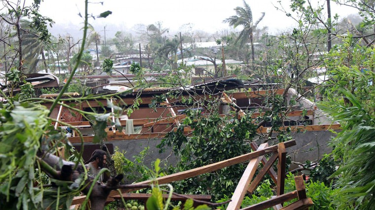 In this photo provided by non-governmental organization 350.org, debris is scattered over a building in Port Vila, Vanuatu, Saturday, March 14, 2015, in the aftermath of Cyclone Pam. Winds from the extremely powerful cyclone that blew through the Pacific's Vanuatu archipelago are beginning to subside, revealing widespread destruction. (AP Photo/350.org, Isso Nihemi)