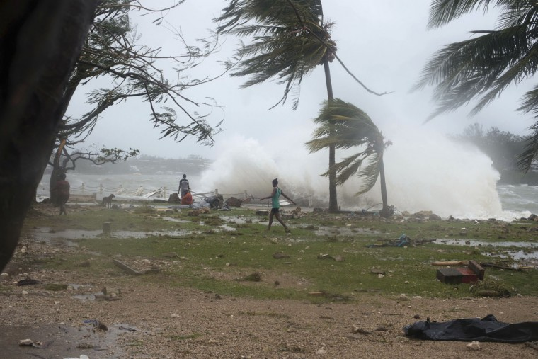 In this image provided by UNICEF Pacific people walk along the shore where debris is scattered in Port Vila, Vanuatu, Saturday, March 14, 2015, in the aftermath of Cyclone Pam. Winds from the extremely powerful cyclone that blew through the Pacific's Vanuatu archipelago are beginning to subside, revealing widespread destruction. (AP Photo/UNICEF Pacific, Humans of Vanuatu)