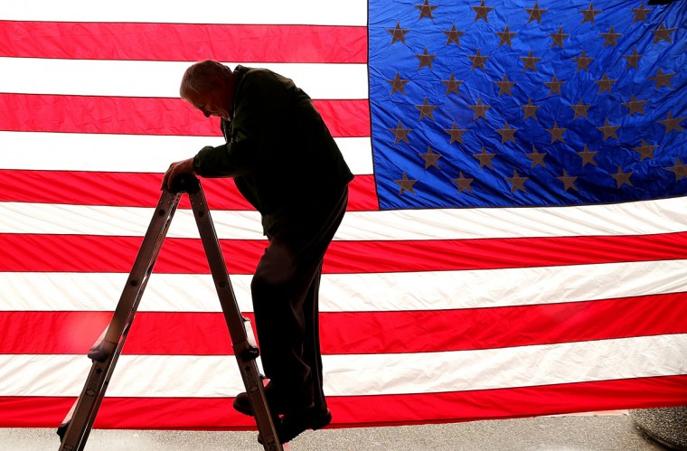 In this photo taken Monday, March 23, 2015, Dale Nitz carefully climbs down his ladder after hanging a large American flag in front of his Veterans Living History Museum on Bay Street in downtown Port Orchard,Wash. (AP Photo/Kitsap Sun, Meegan M. Reid)