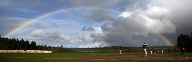 In this photo taken on Monday, March 23, 2015, a rainbow stretches over the field as the Eagles take on the Vikings during a baseball game in Silverdale, Wash. (AP Photo/Kitsap Sun, Meegan M. Reid)