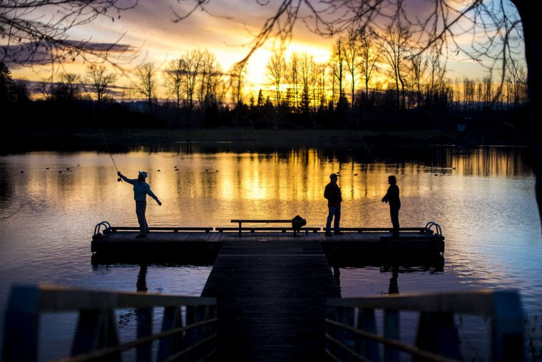 Bill Vasek, left, and his wife, Connie, right, take fly fishing lessons from Steve Buckner, of Toledo, at South Lewis County Park Pond at sunset on Tuesday, Feb. 24, 2015 in Toledo, Wash. The Tumwater, Wash. couple said they are planning a trip to Mexico to go bone fishing in March. (AP Photo/The Chronicle, Pete Caster)