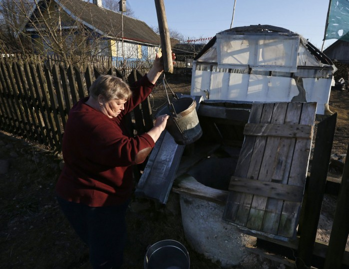 A woman uses a bucket to fetch water from the draw-well on her farmstead in the village of Lovtsevichi, 45 km (28 miles) northwest of Minsk, Belarus, on Monday, March 16, 2015. In villages where there is no central water supply, draw-wells are the only source of drinking water. Water quality is usually dependent on the depth. (AP Photo/Sergei Grits)