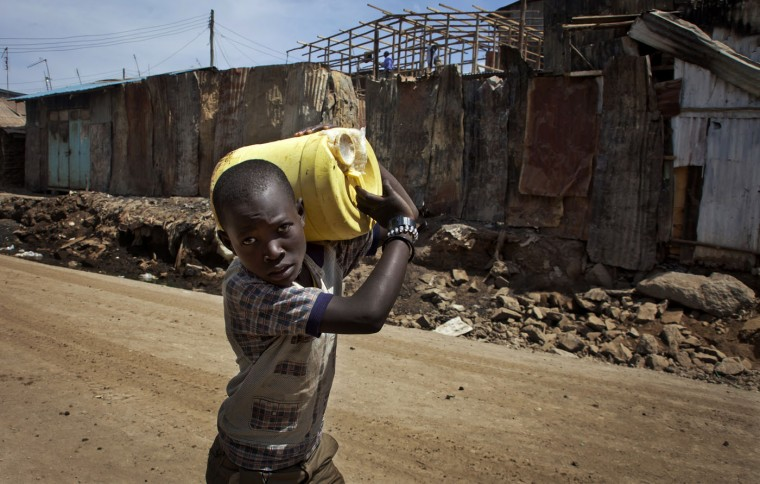 A boy returns home carrying a 20-liter container of fresh water, which cost 5 Kenyan shillings (5.5 U.S. cents) to fill from a private tap in the street, in the Kibera slum of Nairobi, Kenya, on March 14, 2015. (AP Photo/Sayyid Azim)