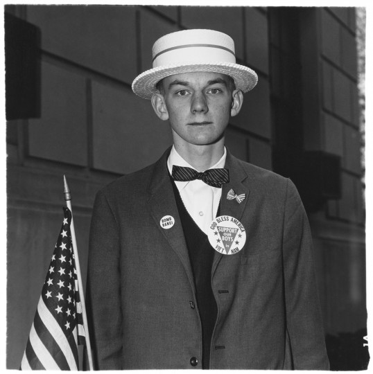 """Boy with a straw hat waiting to march in a pro-war parade, (Diane Arbus)"